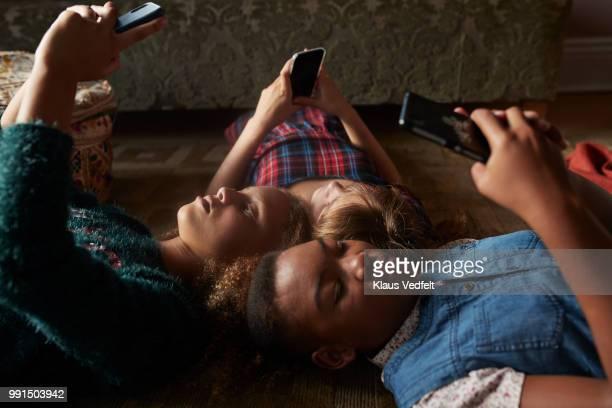 3 tween girls looking at their smartphones