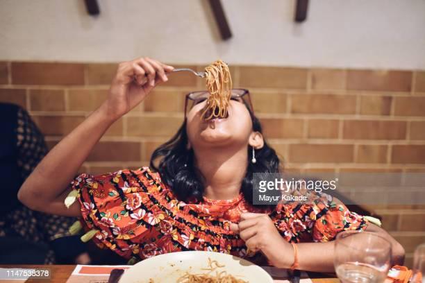 tweenage girl eating noodles - noodle foto e immagini stock