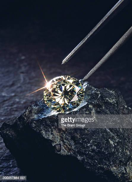 tweezers above diamond on piece of coal, close-up - diamant stock pictures, royalty-free photos & images