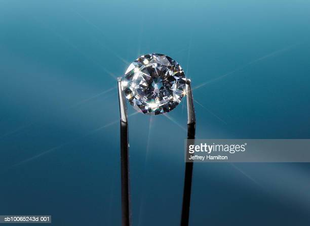 Tweezers holding diamond, close-up