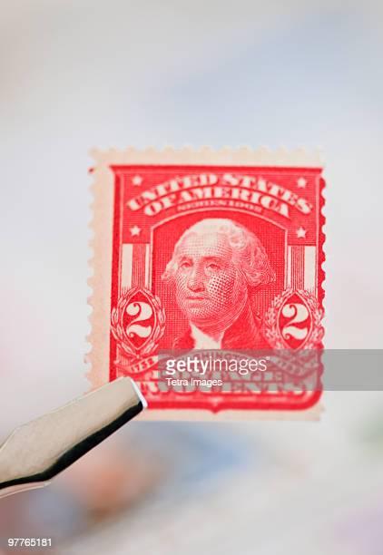 Tweezers holding stamp