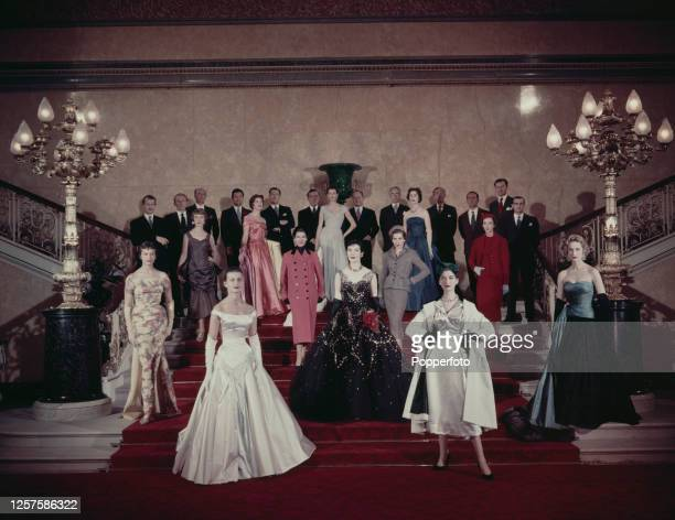 Twelve male fashion designers from the Incorporated Society of London Fashion Designers stand together on a grand staircase behind twelve female...