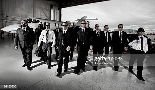 Twelve men walk from executive jet, at hanger