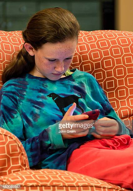 Twelve year old girl reading a text message on her mobile phone device