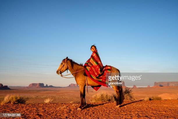 12歳のナバホの女の子は、インドの毛布で夕暮れ時にアリゾナ州北部のモニュメントバレー部族公園で有名なビュートの前に彼女のベイブラウン色の馬の上に座っています - ネイティブアメリカン ストックフォトと画像