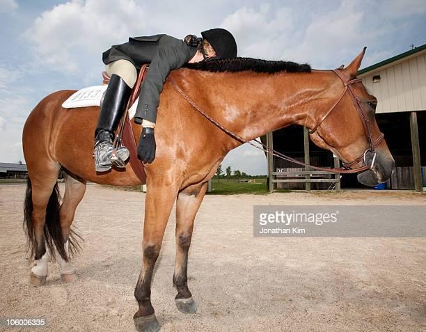 Twelve year old rider sleeps on her horse.