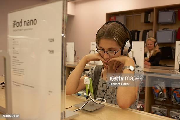 A twelve yearold girl visiting the London branch of the Apple Store in London's Regent Street is listening intently to digital music on a green iPod...