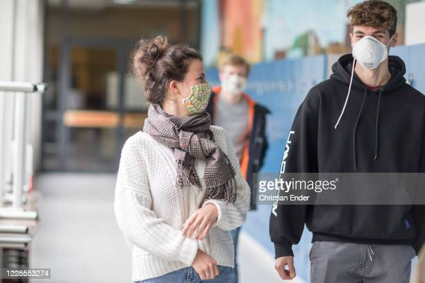 Twelve-graders on the way to a break wear protective face masks and come back to school for the first time since March, whereby the lessons for each...