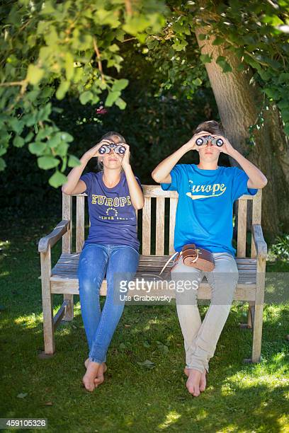 Twelveyearold girl and fourteenyearold boy sitting on a bench in a garden with binoculars on August 11 in Duelmen Germany Photo by Ute...