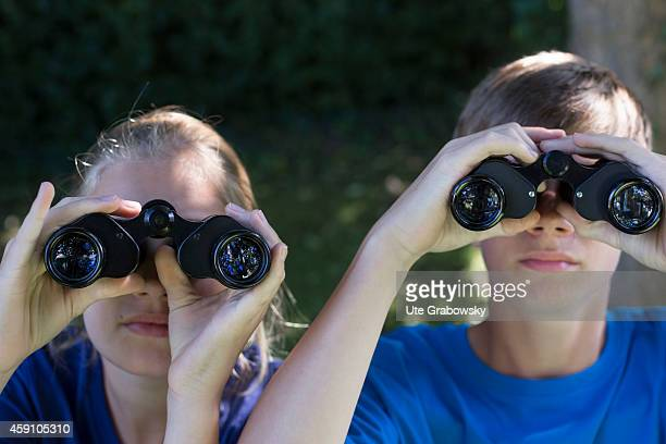 Twelveyearold girl and fourteenyearold boy sitting with binoculars on August 11 in Duelmen Germany Photo by Ute Grabowsky/Photothek via Getty Images