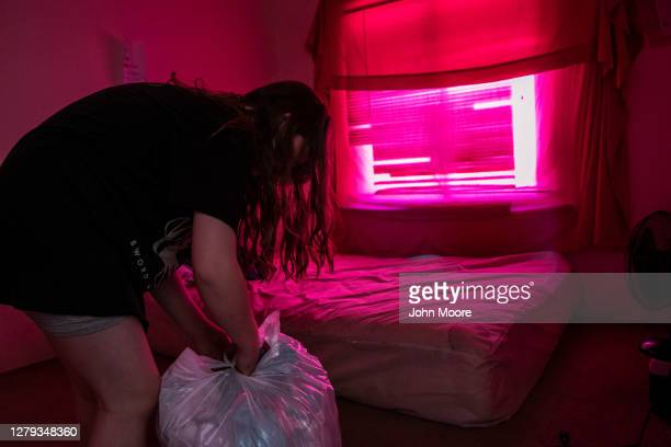 Twelve-year-old girl hurriedly bags up her clothing while being evicted from her family's apartment for non-payment of rent on September 30, 2020 in...