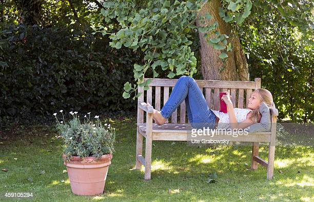 Twelveyearold girl reading a book on a bench in a garden on August 11 in Duelmen Germany Photo by Ute Grabowsky/Photothek via Getty Images