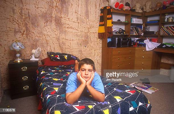 Twelveyearold James Tappin poses for a portrait in his 'dugout' bedroom January 2000 in the opal mining town of Coober Pedy Australia