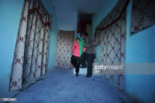 Twelveyearold Tarana Akbari walks down stairs with the help of her uncle at her home in Kabul on December 10 2011 Akbari was photographed crying...