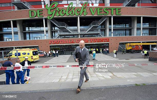 Twente commercial director Jan van Halst leaves the stadium as rescue teams attend the scene after part of the roof of De Grolsch Veste Stadium of...