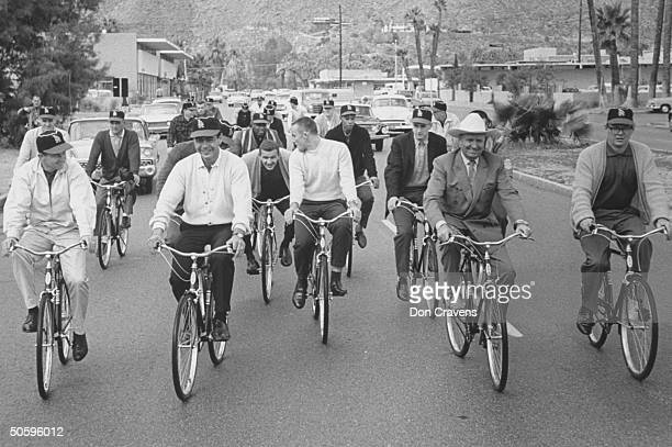 Twenty LA Angels baseball players sporting baseball caps casual clothes as they ride bicycles w C/W singer Gene Autry leading the pack on street...