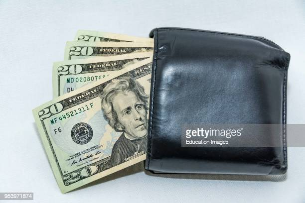 Twenty dollar US bank notes sticking our of a man's billfold