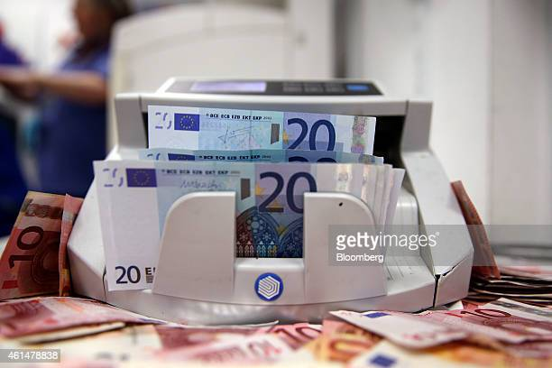 Twenty euro banknotes pass through an automated currency counting machine in this arranged photograph taken inside a Travelex store, operated by...