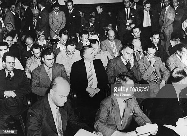 Twenty nine men and women of a Nazi spy ring seated behind FBI officials awaiting arraignment in Brooklyn Federal Court