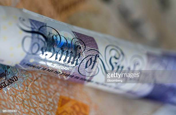 Twenty pound note and ten pound note sit arranged for a photograph in London, U.K., on Thursday, March 25, 2010. The pound had its biggest gain in...