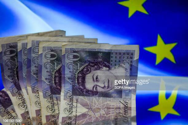 Twenty pounds bank notes are seen with European union flag on the background.