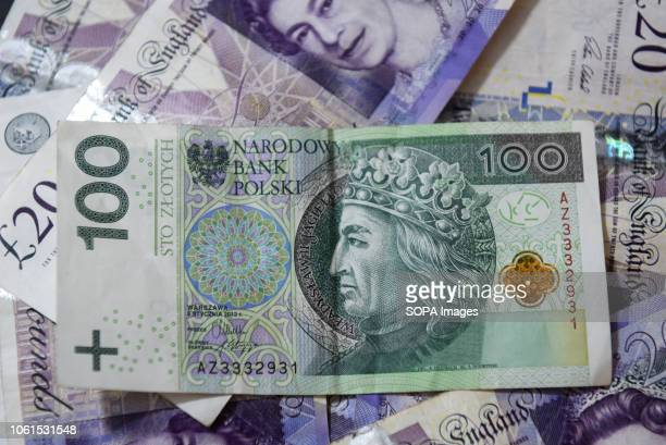 Twenty pounds bank notes, one hundred zloty bank note are seen displayed.