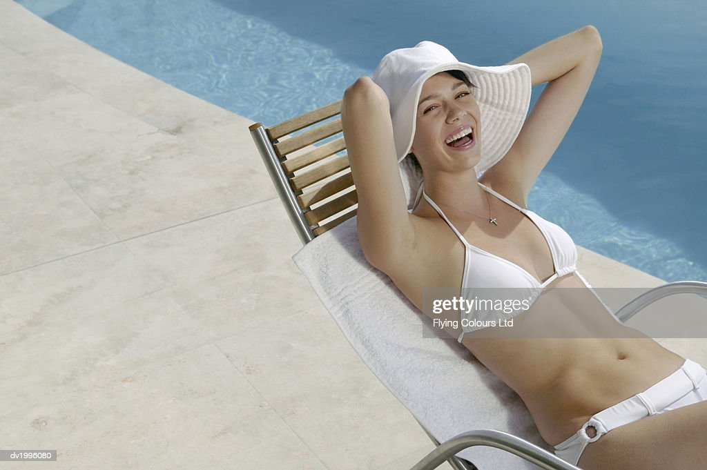 Twenty something Woman Lying on a Sunbed Poolside Wearing a Bikini and Sunhat : Stock Photo