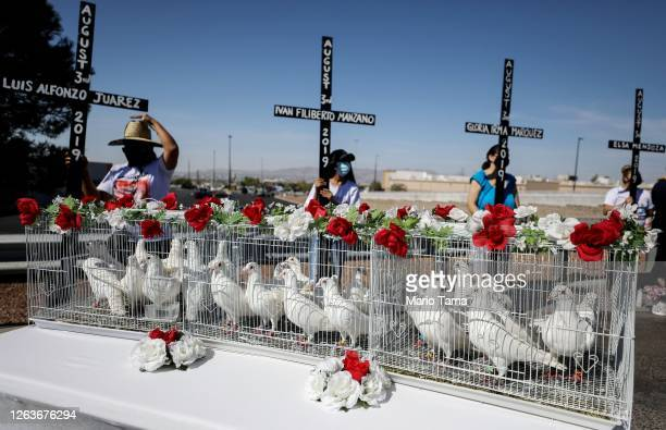 Twenty three doves await release outside Walmart as mourners hold crosses honoring those killed in the Walmart shooting which left 23 people dead in...