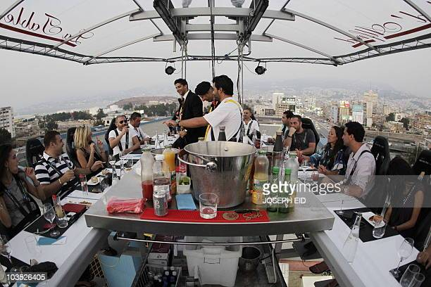 Twenty two men and women suspended 50 meters over a parking lot enjoy their meal at �Dinner in the Sky' on July 10 in Beirut where guests sit...