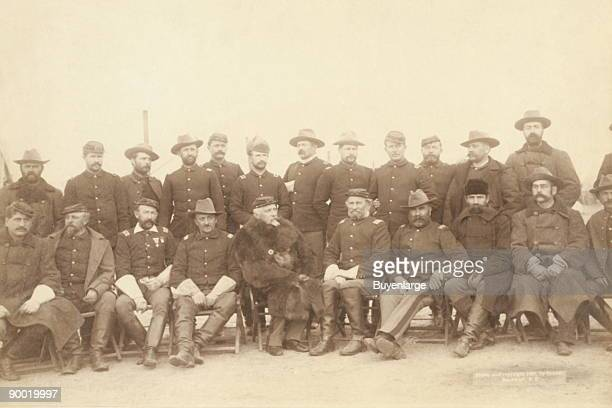 Twenty two uniformed military men standing and sitting in camp chairs Some of the men are wearing winter coats