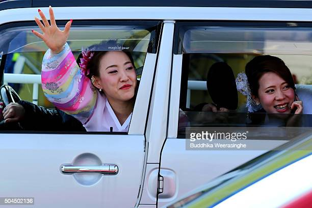 A twenty year old female dressed in Kimono waves from car window while attending the Coming of Age Day ceremony on January 11 2016 in Kobe Japan The...