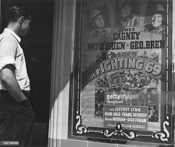 A twenty year old man looks at the movie poster for 'The Fighting 69th' in the town of San Leandro California April 1940 With his high school...