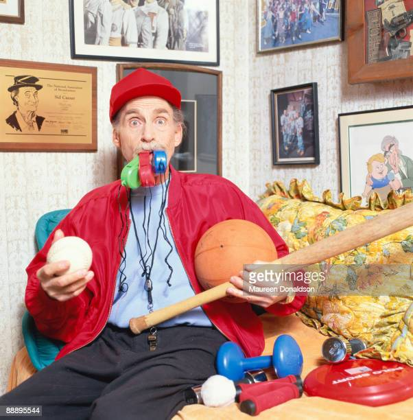 Twenty years on American comic actor Sid Caesar recreates his role as Coach Calhoun in the 1978 musical film 'Grease' On the wall behind him is a...