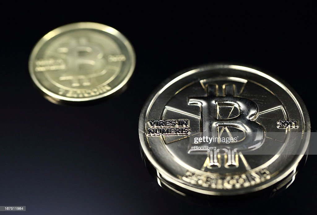 A twenty-five bitcoin, right, and one bitcoin are arrange for a photograph in Tokyo, Japan, on Thursday, April 25, 2013. The digital currency, which carries the unofficial ticker symbol of BTC, was unveiled in 2009 by an unidentified programmer, or group of programmers, under the name of Satoshi Nakamoto. Supply is capped at 21 million Bitcoins and managed by a software algorithm embedded into the digital currency's design, rather than a monetary authority such as a central bank. Photographer: Tomohiro Ohsumi/Bloomberg via Getty Images
