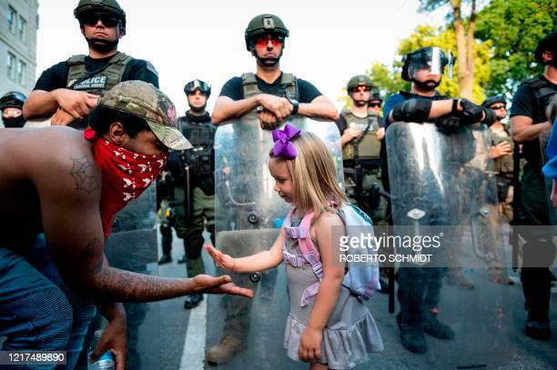 Twenty-nine-year old DC resident, George , slaps hands with three-year-old Mikaela in front of a police barricade on a street leading to the front of...