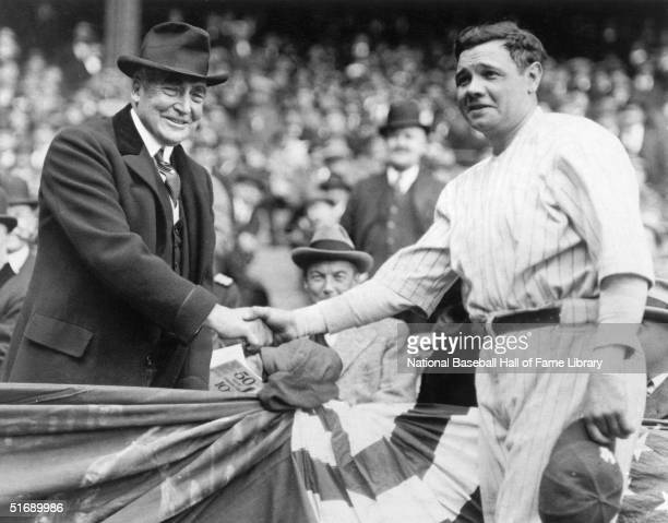 Twentyninth President of the United States Warren G Harding and Babe Ruth of the New York Yankees shake hands as they pose for a photo during a 1922...