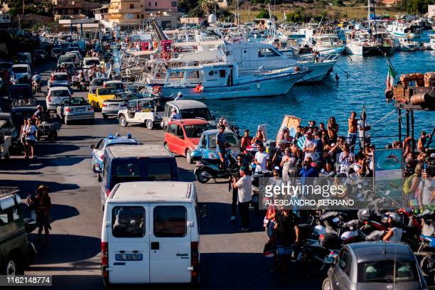 Twenty-seven unaccompanied minors leave the harbour in Lampedusa in police vans on August 17 after being evacuated from the Spanish migrant NGO...