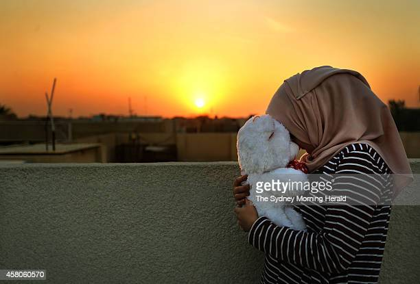 A twentysixyearold teacher looks across the rooftops of Baghdad Iraq and holds the teddy bear she received from her new husband October 23 2014 The...
