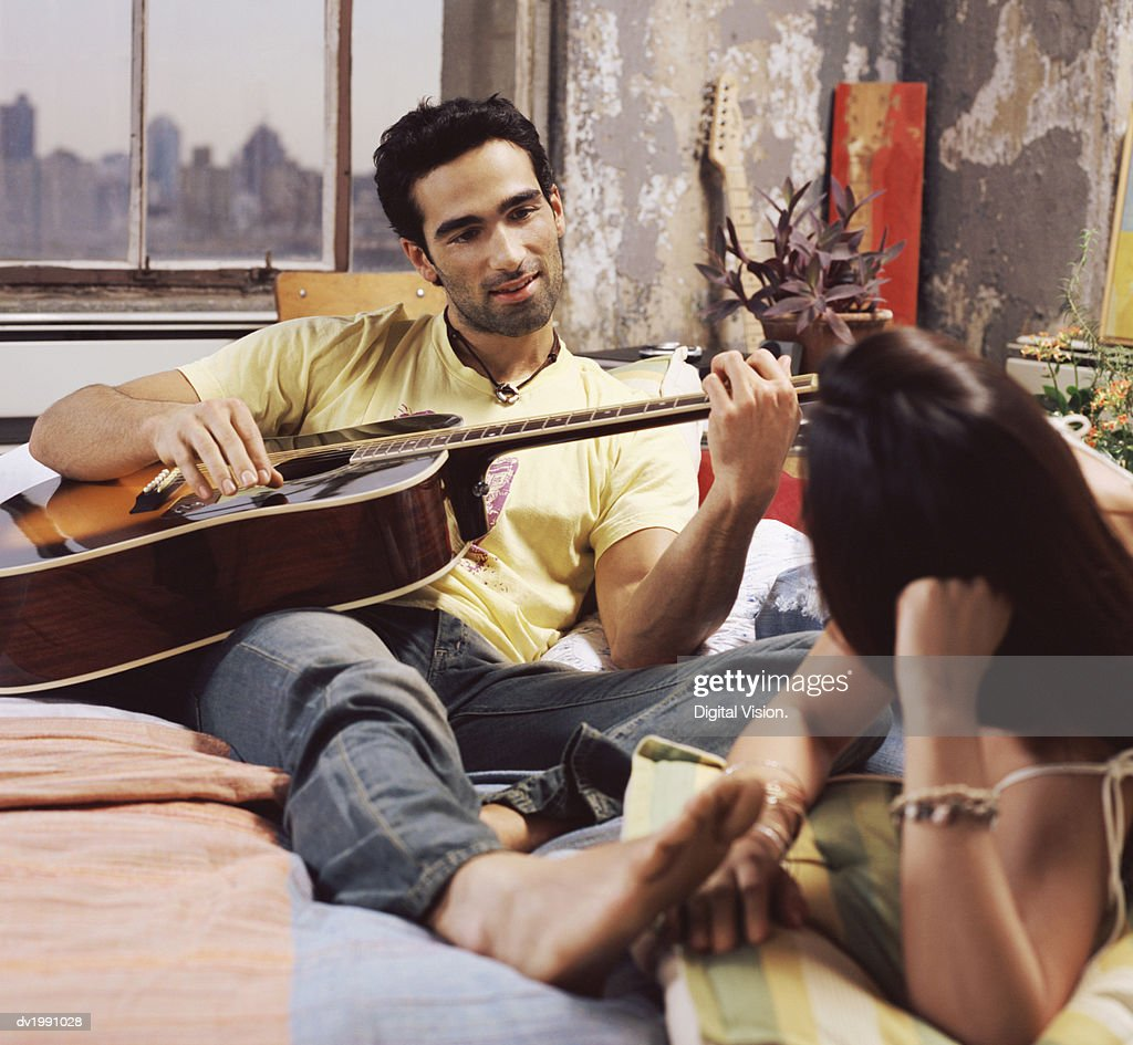 Twentysomething Couple on a Bed in an Apartment, Man Playing an Acoustic Guitar : Stock Photo