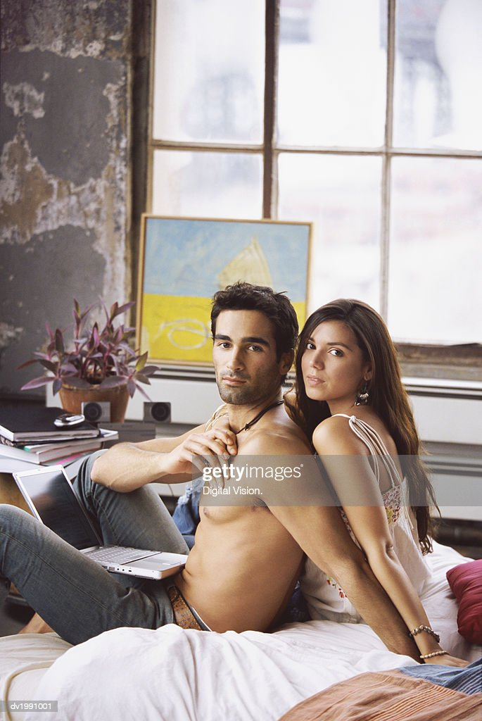 Twentysomething Couple Sitting on a Bed in an Apartment : Stock Photo