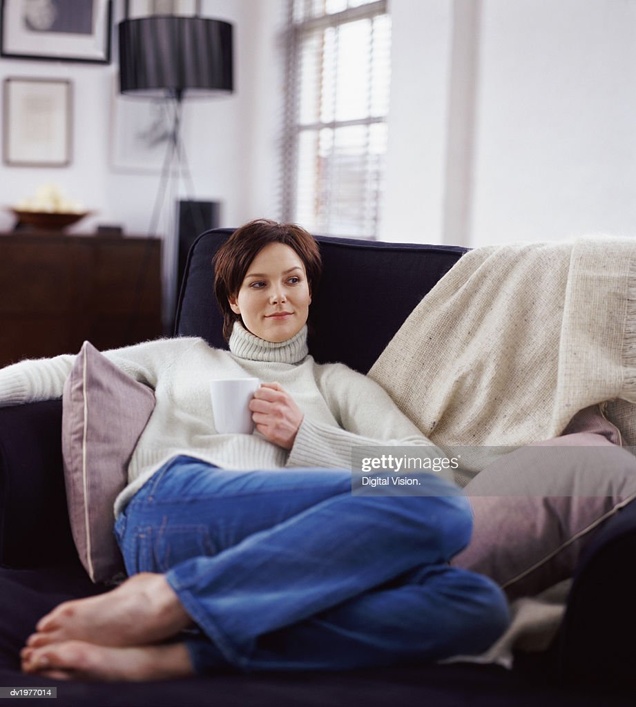 Twentysomething Woman Sitting on a Sofa and Holding a Coffee Cup : Stock Photo