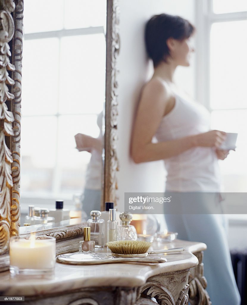 Twentysomething Woman Standing by an Ornately Designed Dressing Table and Mirror : Stock Photo