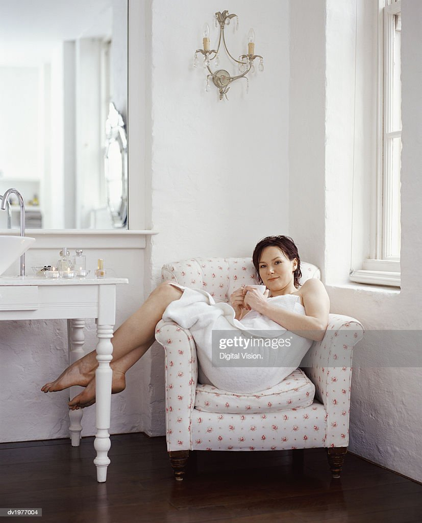 Twentysomething Woman Wrapped in a Towel Sitting in an Arm Chair in a Showcase Bathroom : Stock Photo