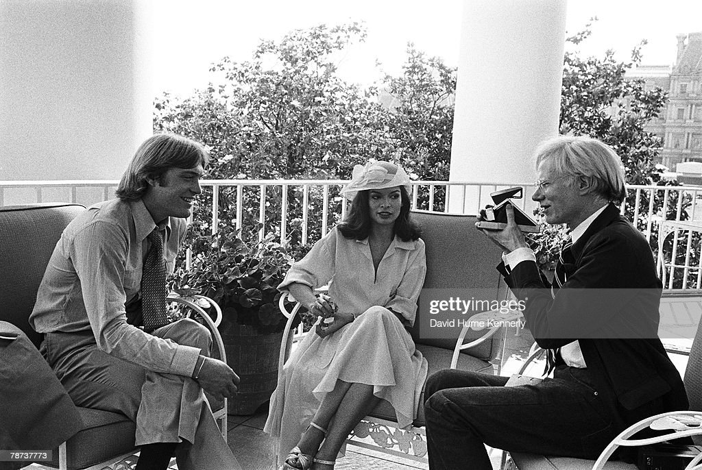 Twenty-three-year-old Jack Ford, who frequently hosted notable visitors at the White House, poses for a Polaroid portrait on the South Portico's Truman Balcony with his guests, Andy Warhol and Bianca Jagger July 2, 1975 in Washington, DC.