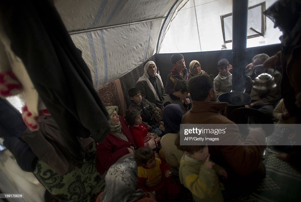 Twenty-two members of the same Syrian family from the city of Marea in the countryside of Aleppo, including three young relatives with down syndrome and other mental disorders sit inside their tent waiting for their next meal, at a refugee camp in Bab al-Salama on the Syria-Turkey border, on January 9, 2013. The internally displaced Syrians faced further misery due to increasing shortage of supplies as heavy rain was followed by a drop in temperatures.
