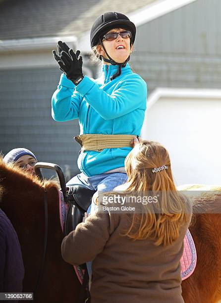 Twentyyear old Stephanie Hart who suffers from cerebral palsy claps in approval as she rides a horse at Equine Partners a therapeutic equestrian...