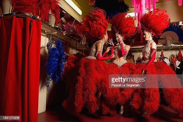 Twenty-year-old dancer Morgan Kenny poses with dancers Katie Hayward and Jessie Toone backstage at the Moulin Rouge on September 13, 2011 in Paris,...