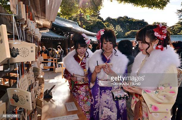 Twentyyearold female tour guides dressed in traditional kimonos hang up 'ema' or votive tablets with their written wishes at Tokyo's Meiji Shrine...