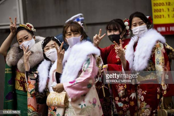 """Twenty-year-old women dressed in kimonos flash victory sign outside Todoroki Arena during the """"Coming-of-Age Day"""" celebration ceremony in Kawasaki,..."""