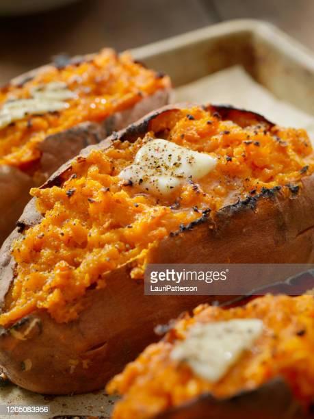 tweemaal gebakken, gevulde zoete aardappel met boter en gebarsten peper - eetklaar stockfoto's en -beelden